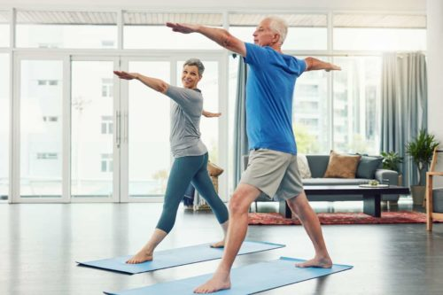 mature couple practicing yoga at home