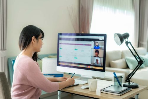 businesswoman on conference call with coworkers working remotely