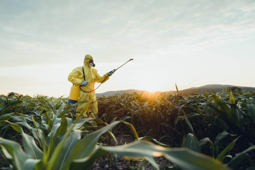 farmer in hazmat spraying fields with herbicde