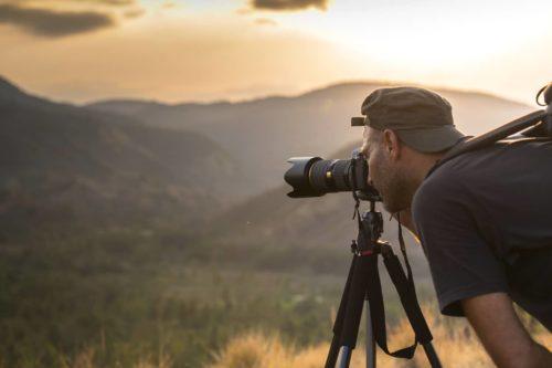 nature photographer taking photo on tripod